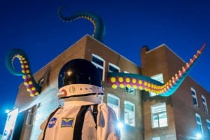 Beakerhead art installation, tentacles coming out of building with astronaut in the foreground